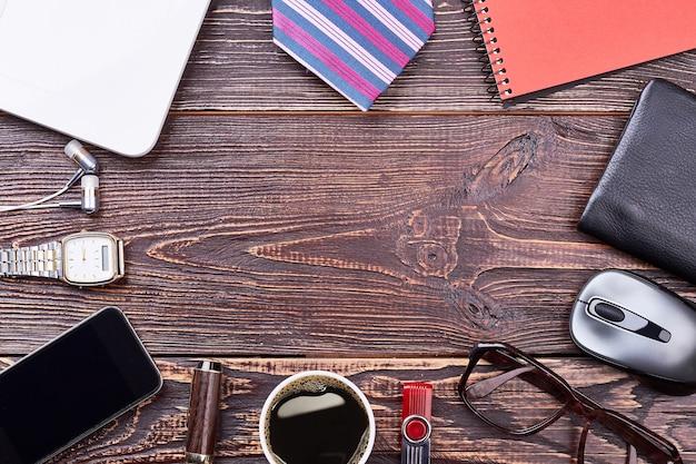 Smartphone, caffè e bicchieri. taccuino e penna su legno. atmosfera di lavoro formale.