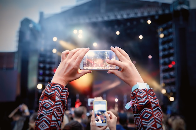 Smartphone sopra la folla a un concerto di musica. registra spettacolo di luci