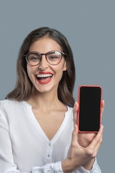 Smartphone, delizia. giovane donna dai capelli lunghi con gli occhiali e in camicetta bianca che mostra smartphone con gioia
