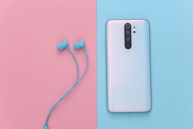 Smartphone e auricolari su pastello blu-rosa