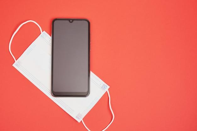Smartphone e maschera facciale su sfondo rosso, cose necessarie per uno spazio di copia vista dall'alto di una persona moderna