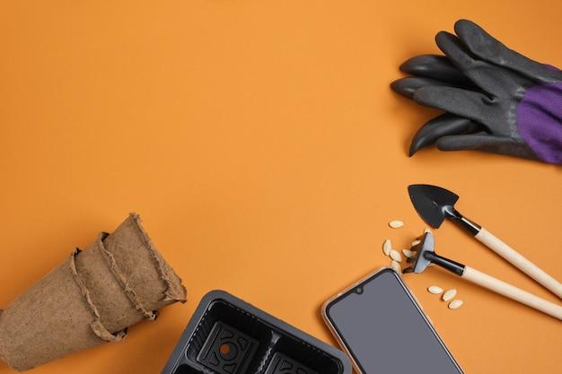 Smartphone e attrezzatura da giardino su sfondo marrone, concetto di blog giardiniere