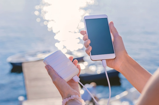 Smartphone in mano a una ragazza sul molo. ricarica il tuo telefono con power bank. sullo sfondo di un fiume, lago, con un ponte e barche.
