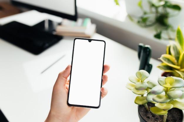 Smartphone in mano, lavoro da casa, ufficio. foto di alta qualità