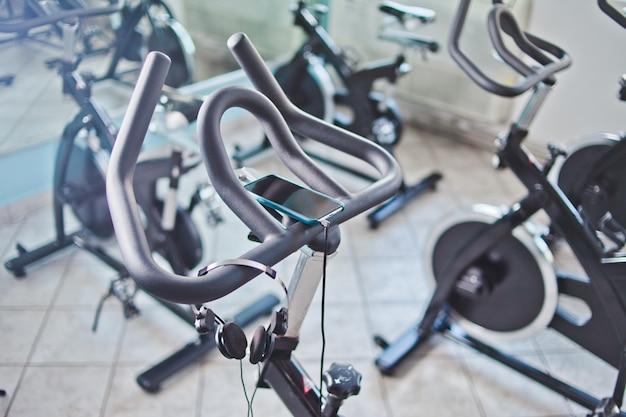 Smartphone e cuffie che appendono sulla bici fissa alla classe di filatura