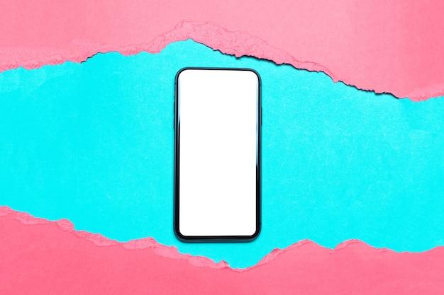 Smartphone nel foro di carta rosa strappata sul colore ciano.