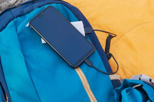Lo smartphone viene caricato con un caricabatterie portatile. power bank con un telefono cellulare su un sacco a pelo con uno zaino.