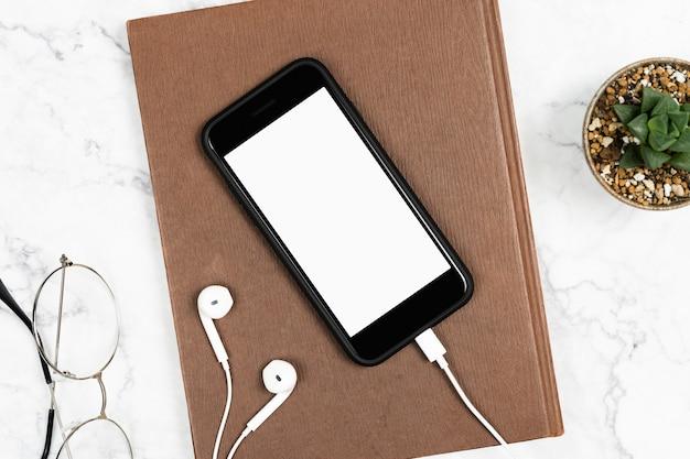 Smartphone ha isolato lo schermo bianco con gli earphones collegati e taccuino sullo scrittorio