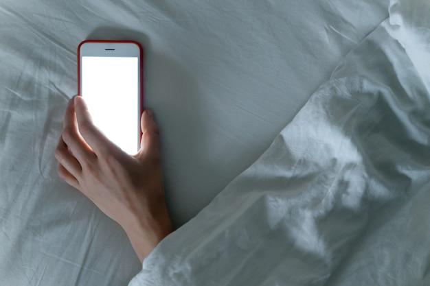 Smartphone in posa in mano della donna addormentata sotto coperta