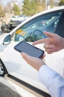 Smartphone in mani maschili per strada, sullo sfondo dell'auto.
