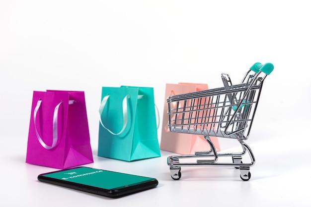Smartphone, mini carrello con carte di credito e sacchetti di carta colorati isolati su bianco, e-commerce