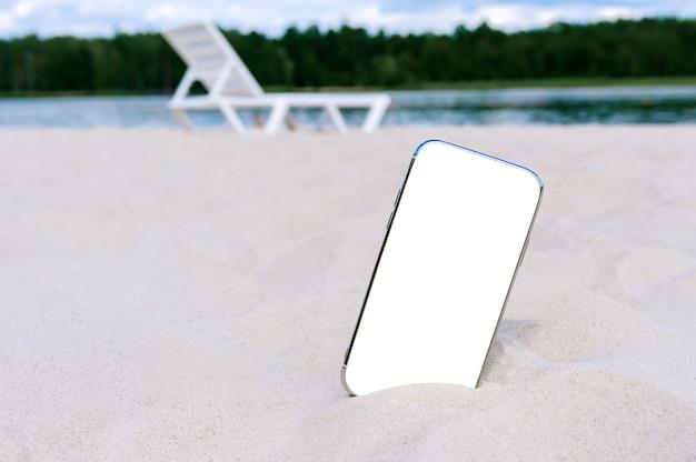 Modello di smartphone nella sabbia sulla spiaggia. sullo sfondo di un lettino prendisole, acqua e alberi. concetto sul tema del viaggio.
