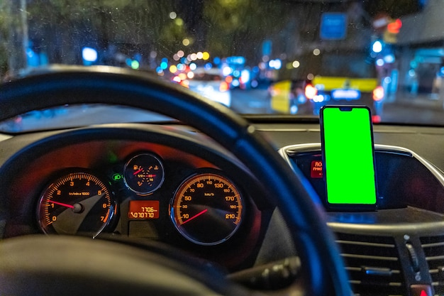 Mockup di smartphone con schermo verde in macchina durante la guida per aggiungere gps o app