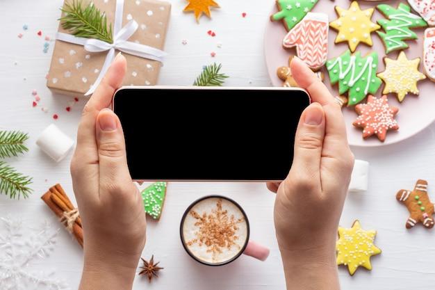 Mockup di smartphone nelle mani di donna su sfondo bianco di natale con pan di zenzero e dolci