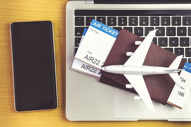 Smartphone vicino al computer portatile e aereo sul tavolo. concetto di prenotazione di biglietti online