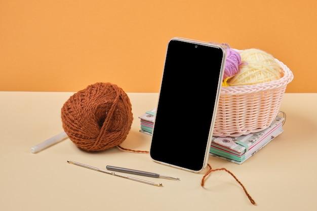 Smartphone, notebook e ganci e fili per maglieria in un cestino, formazione online sul lavoro a maglia