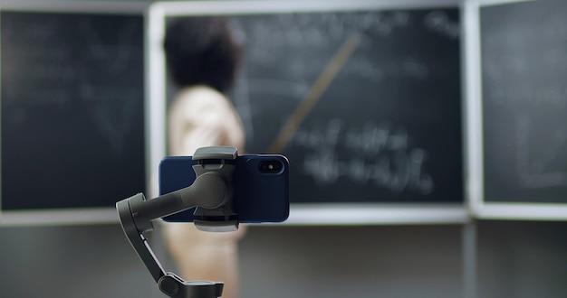 Video lezione di registrazione dello smartphone a scuola. studio in linea. giovane insegnante femminile afroamericana che spiega le formule di matematica o di fisica in classe. concetto di quarantena. studio durante il coronavirus.
