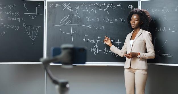 Smartphone che registra video lezione virtuale sulla webcam a scuola. studio in linea. docente di donna afro-americana che insegna formule di matematica o fisica alla lavagna. concetto di blocco. studio pandemico.