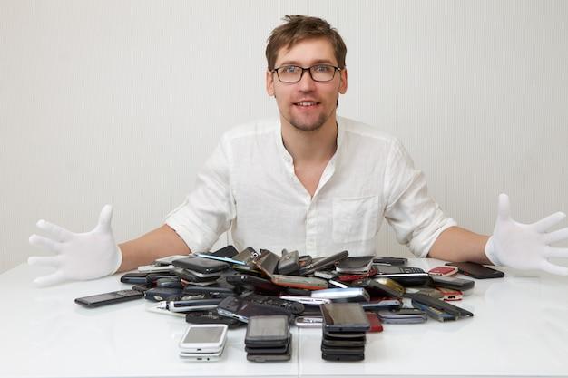 Un riparatore di smartphone è felice di riparare un'enorme pila di telefoni rotti