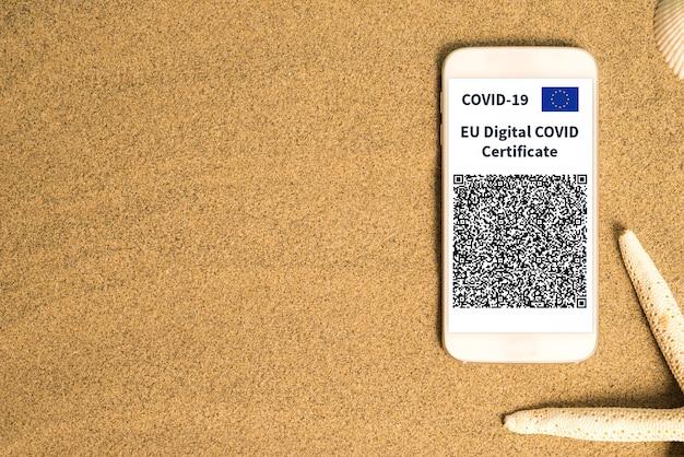 Smartphone sulla sabbia con un certificato europeo di vaccino contro il covid o green pass sullo schermo