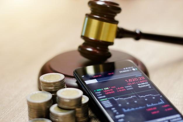 Smartphone che mostra la tendenza del mercato azionario e il martelletto del giudice, moneta sul tavolo