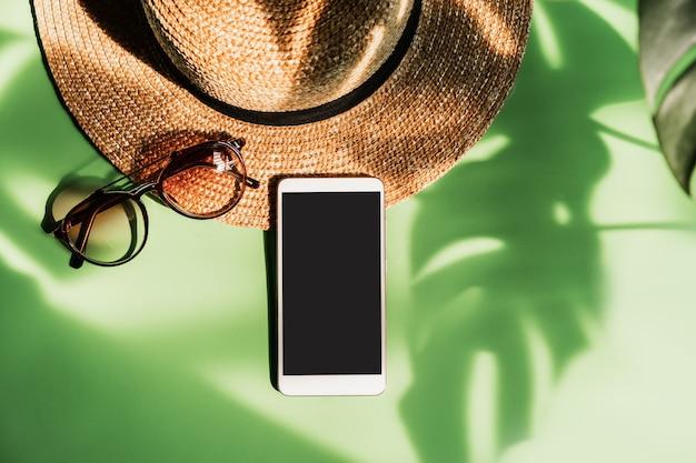 Smartphone, occhiali da sole e cappello su sfondo verde con ombra di foglie tropicali tropical