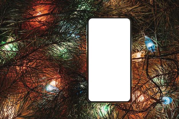 Smartphone circondato da albero di natale e accessori. smartphone circondato da rami di abete. schermo vuoto per design o testo. decorazioni natalizie e concetto di tecnologia.
