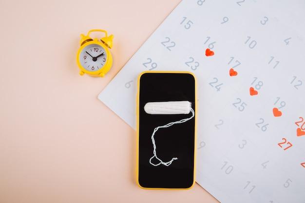 Smartphone per monitorare il ciclo mestruale e per i segni. pms e il concetto dei giorni critici. tampone di cotone e allarme giallo su sfondo rosa.