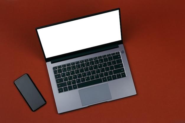 Smartphone e un mockup bianco sullo schermo di un laptop su una vista dall'alto di sfondo marrone