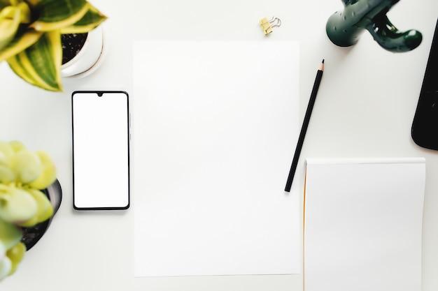 Smartphone sul tavolo bianco, lavoro da casa, roba da ufficio. foto di alta qualità