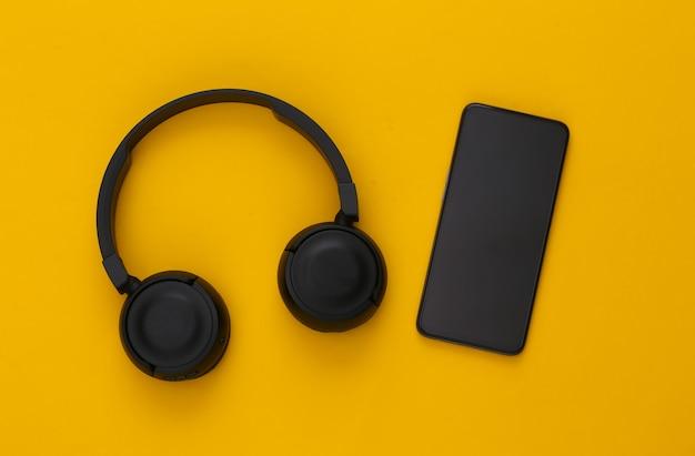 Smartphone con cuffie stereo nere su sfondo giallo