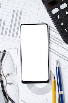 Smartphone con uno schermo vuoto sullo sfondo di grafici e tabelle. copia spazio. il concetto di investimento online o commercio di azioni o affari.