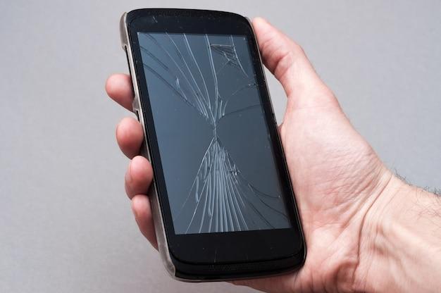 Smartphone con schermo rotto in mano