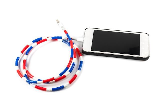 Smartphone con cavo di ricarica su superficie bianca