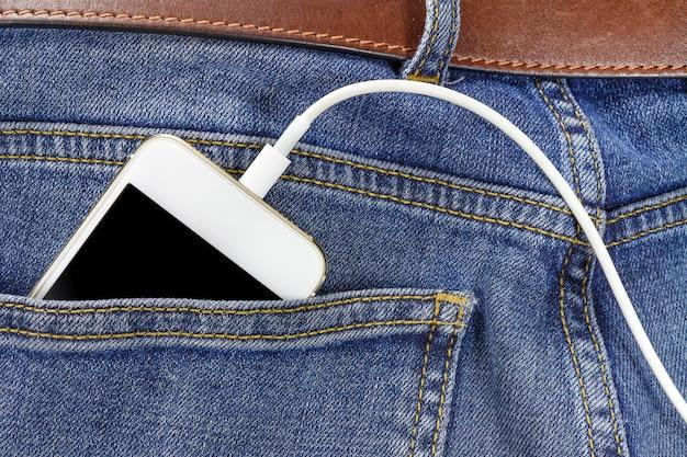 Smartphone con cavo di collegamento usb nella tasca posteriore del primo piano dei jeans