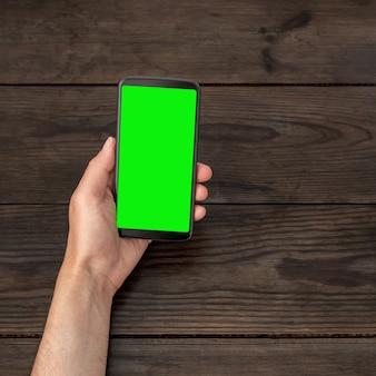 Smartphone con uno schermo verde in mano su uno sfondo di tavolo in legno.