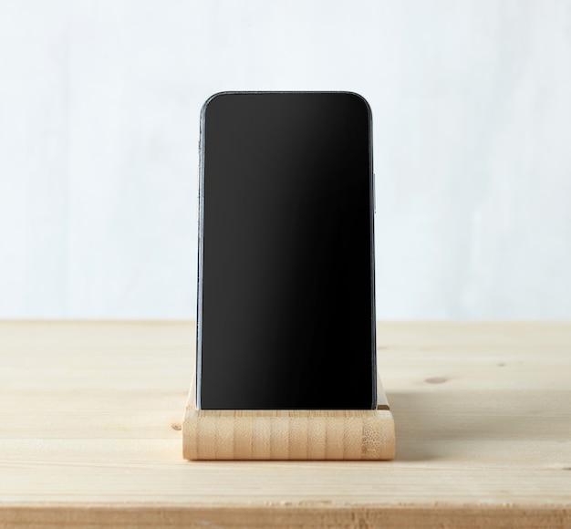 Smartphone in legno su tavolo in legno chiaro