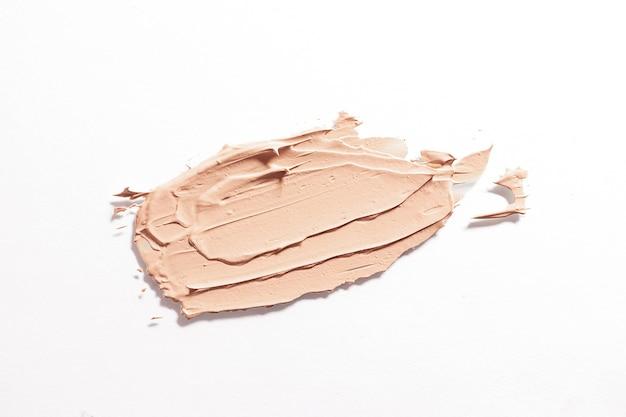 Sbavatura di fondazione isolato su sfondo bianco. il concetto di cosmetici decorativi, trucco. macro fotografia pubblicitaria.
