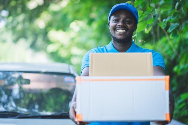 Sorriso uomo corriere consegna postale africano davanti all'auto che consegna il pacchetto