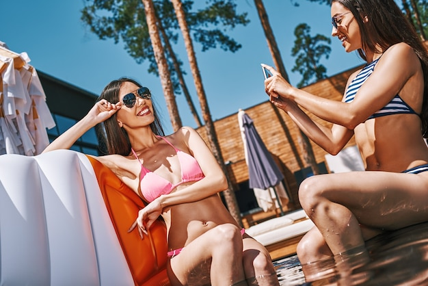 Sorridi bella giovane donna in costume da bagno che fa foto della sua amica mentre è seduta vicino