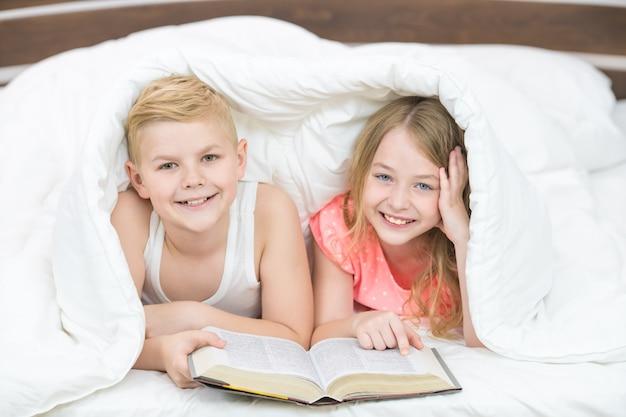 Il ragazzo e la ragazza sorridenti con un libro giacevano sotto il piumone