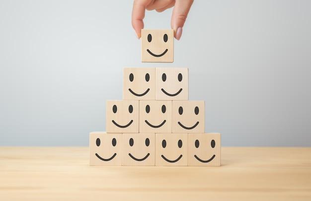 Smile face simbolo felice su blocco di legno, servizi e concetto di indagine sulla soddisfazione del cliente. servizio clienti e concetto di valutazione della soddisfazione dell'esperienza. piramide di sorrisi