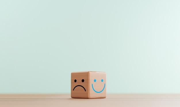 Schermata di stampa del viso sorridente su blocco cubo di legno luminoso e faccia di tristezza sul lato oscuro per la valutazione del servizio clienti e il concetto di mentalità emozionale mediante rendering 3d.
