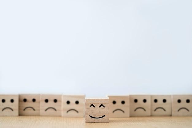 Schermo di stampa del viso di sorriso sul cubo di blocco di legno davanti alla faccia di tristezza.