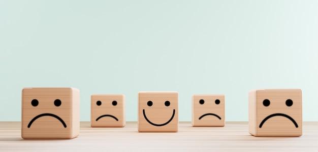 Schermata di stampa del viso sorridente su blocco cubo di legno tra la faccia della tristezza per la valutazione del servizio clienti e il concetto di mentalità emozionale mediante rendering 3d.
