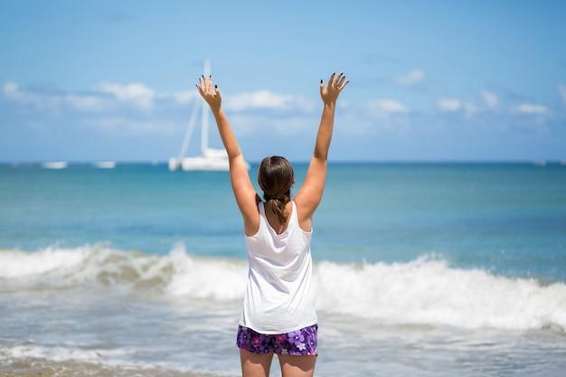 Sorriso libertà e felicità donna sulla spiaggia. si sta godendo la serena natura oceanica durante le vacanze di viaggio all'aperto