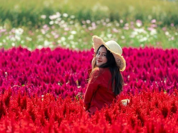 Sorridi felice donna asiatica in un colorato rosso celosia flower garden lady in camicia rossa e cappello a tesa larga