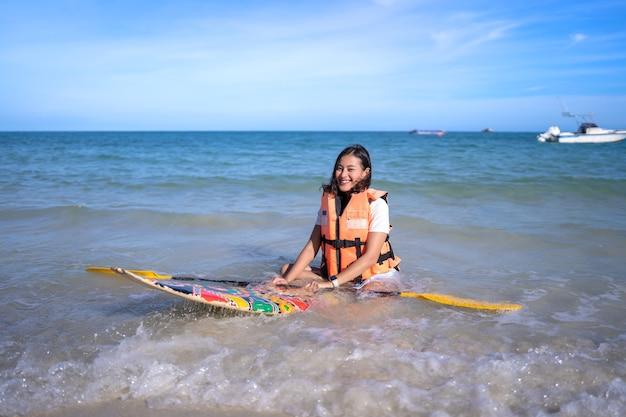 Sorridere felice donna asiatica con giacca salvavita sedersi su un piccolo paddleboard tenendo il remo sulla spiaggia del mare ondulato, la ragazza si rilassa in vacanza in estate