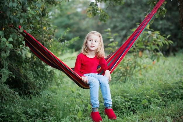 Sorriso bambina bionda in amaca in giardino