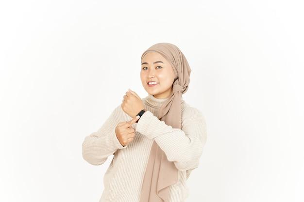 Sorriso e indicando l'orologio della bella donna asiatica che indossa l'hijab isolato su sfondo bianco